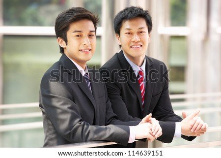 Two Chinese Businessmen Outside Modern Office - stock photo