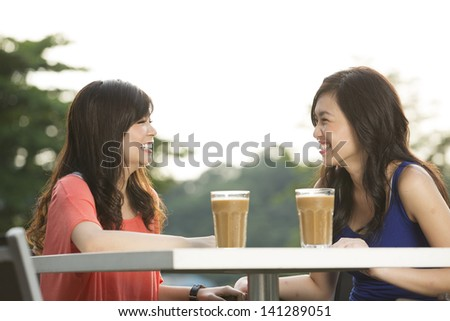 Two Chinese female friends Enjoying Cup Of Coffee - stock photo
