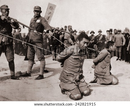 Two Chinese men kneeling prior to execution by Chinese soldiers. The Sino-Japanese war (1937-1945) Fight against the Japanese occupation as well as a civil war between the Nationalists and Communists. - stock photo