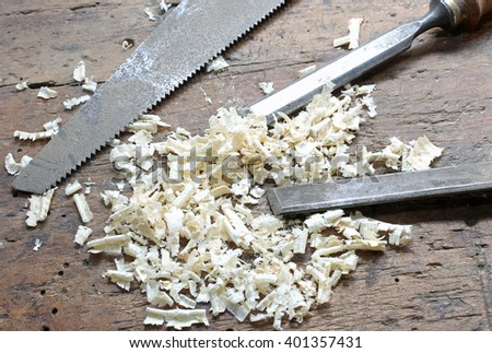two chisels and a hand saw with wood chips in the Workbench with a wooden grip inside the craftsman joinery manufacturer - stock photo