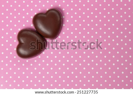 two chocolate candy heart on background with polka dots, valentines day - stock photo