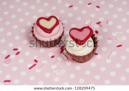 Two chocolate cupcake bonbons with hearts and sprinkles