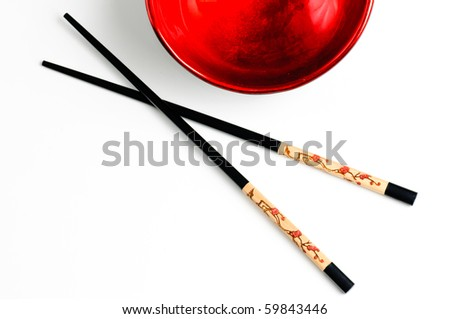 Two chopsticks next to a black and red bowl - stock photo