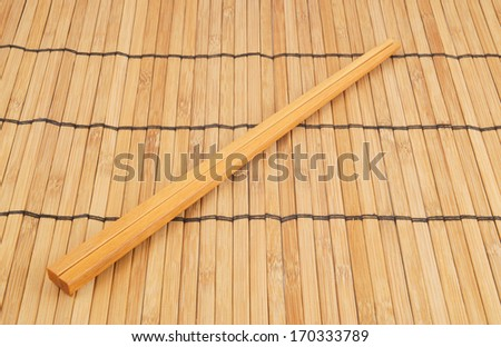 Two chopsticks on brown bamboo background - stock photo