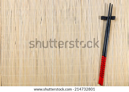 Two chopsticks on sushi mat background - stock photo