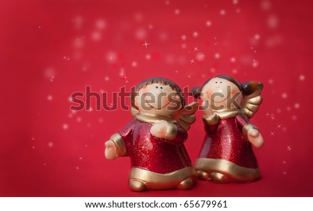 Two Christmas angels figurines on the red background - stock photo