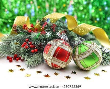 Two Christmas baubles with traditional decorations, berries and conifer branches on green defocused background with bokeh lights - stock photo