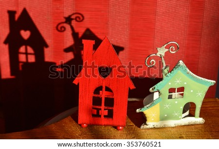 Two Christmas candle holders-houses with shadows on red background - stock photo