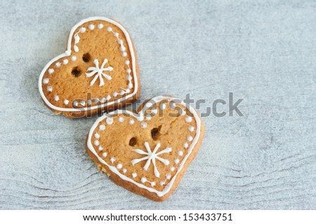 Two Christmas gingerbread heart, decorated with icing on a wooden table - stock photo