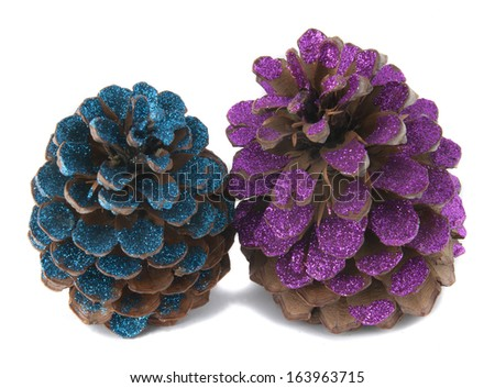 two christmas pinecones painted with colored glitter - stock photo