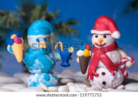 Two christmas snowmen on sea beach - stock photo