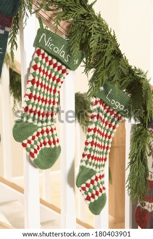 Two Christmas stockings with name Nicolas and Logan on stair bannister  - stock photo