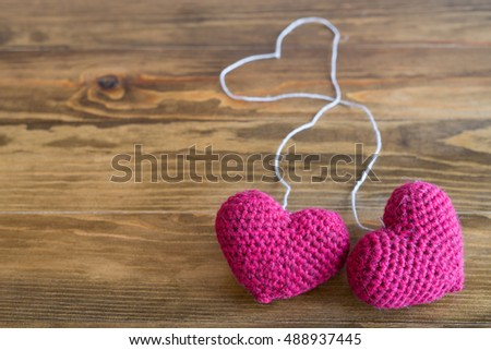 Two chrocheted hearts with threads