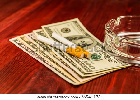 Two cigarettes and glass ashtray are on the dollars