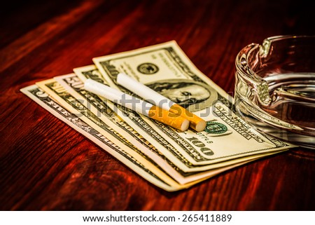 Two cigarettes and glass ashtray are on the dollars. Image vignetting