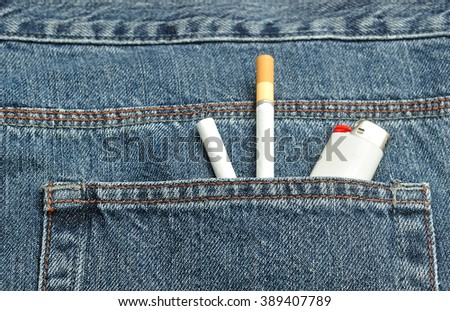 Two cigarettes with a lighter in the back pocket of a denim jeans pants - stock photo