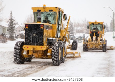 Two city plows clearing snow from the streets.