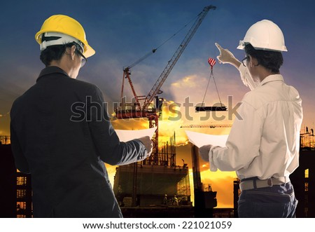 two civil engineer working in building construction site against beautiful dusky sky with crane construction - stock photo