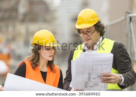 Two civil engineers, a man and a beautiful woman, working - stock photo