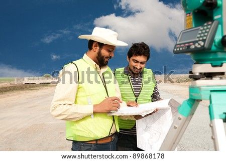 two civil engineers doing land survey at a construction site - stock photo