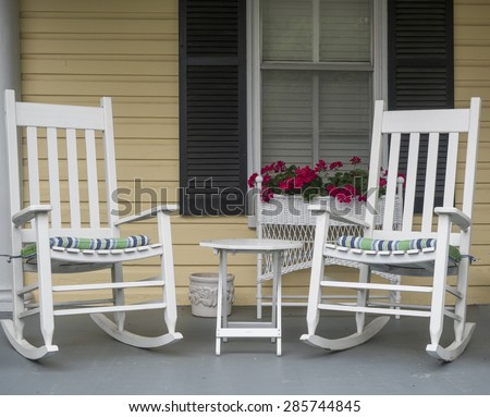 Two classic American rocking chairs on the front porch of a home. - stock photo