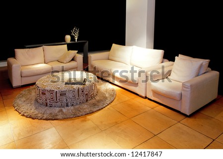 Two classic sofas and armchair in living room at night - stock photo