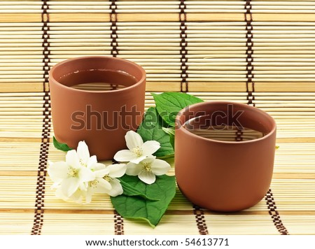 Two clay cups with jasmin green tea - stock photo