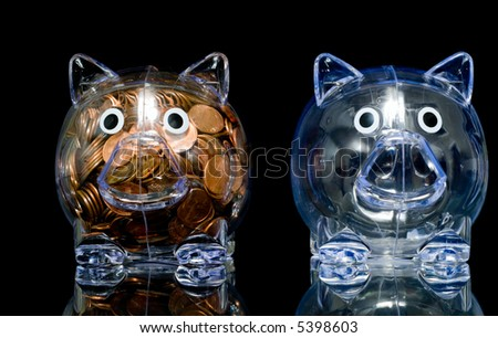 """Two clear acrylic piggy banks one stuffed full of american pennies the other empty, Illustration of the """"haves"""" and the """"have nots"""" - stock photo"""