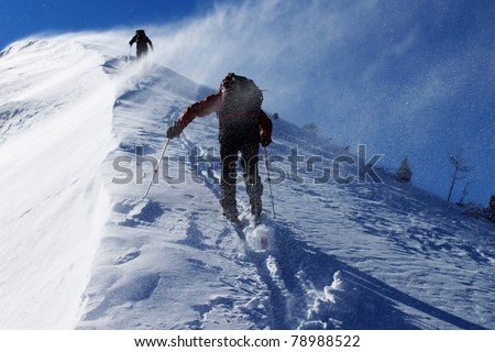 Two climbers ascending snow ridge in snow storm - stock photo