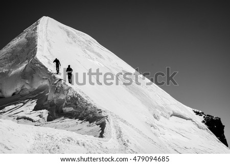 Two climbers on the glacial summit ridge
