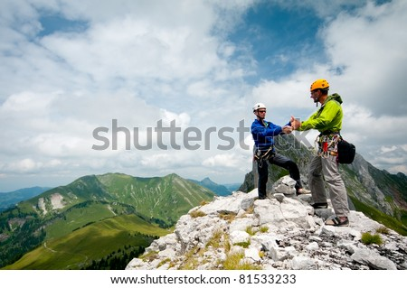 two climbers shake hands on the summit to celebrate success - stock photo