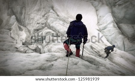 Two climbers walk along a glacial stream in the Alps, Switzerland - stock photo