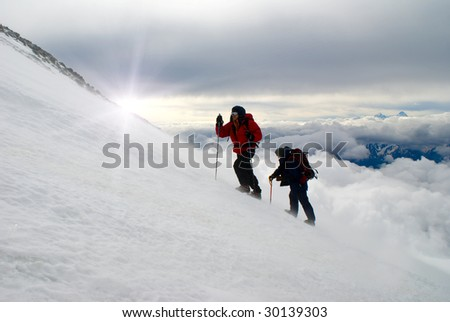 Two climbers walk up the top of mountain - stock photo
