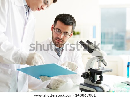 Two clinicians discussing medical document in laboratory - stock photo
