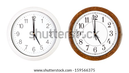 Two clock faces showing five o'clock isolated on white - stock photo