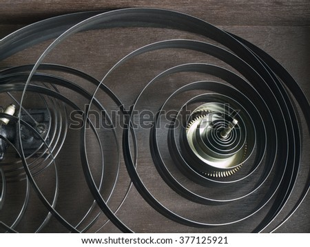 Two clock springs unwound. The springs and one cog wheel are lying dismantled in the wood casing of a pendulum clock. A visual metaphor for absence of stress. - stock photo