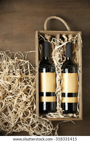 Two closed wine bottles lying on straw in vintage wooden box on wood background. Top view point. - stock photo