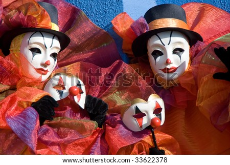Two clowns in bright costumes standing in front of blue wall with mask in the hands Taken at Burano Island during Venice carnival