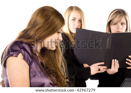 Two co-workers not happy and scowling at the other worker on the computer, showing their dislike.l - stock photo