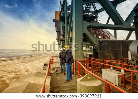 Two coal mine engineers with protective helmets standing on a huge drill machine, talking and watching at the digging site. Beautiful and colorful sky in the background. Rear view. - stock photo