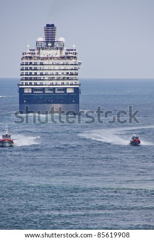 Two coast guard boats leaving blue and white cruise ship sailing out to sea - stock photo
