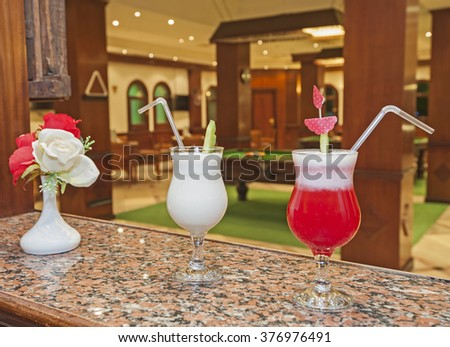 Two cocktail drinks and flowers on a marble bar counter with pool table in background - stock photo