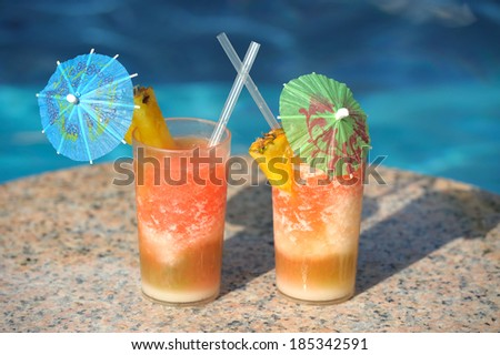 Two cocktail glasses on a marble table by a blue water of swimming pool  - stock photo