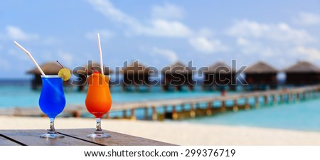 Two cocktails on luxury tropical beach resort, wide panorama  - stock photo