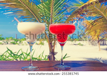 Two cocktails on luxury tropical sand beach - stock photo