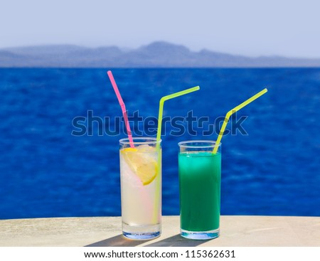 Two cocktails on marble table at beach - travel background - stock photo