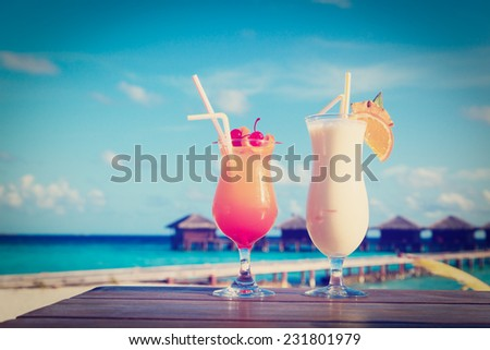 Two cocktails on tropical beach vacation - stock photo
