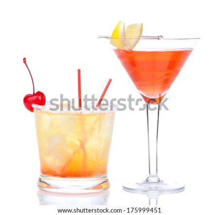 Two cocktails red alcohol cosmopolitan cocktail decorated with citrus lemon in martini cocktails glass and yellow summer margarita isolated on a white background  - stock photo
