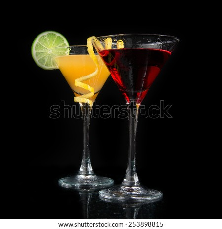 Two cocktails red cosmopolitan cocktail decorated with citrus lemon twist and yellow martini margarita drink with lime on a black background