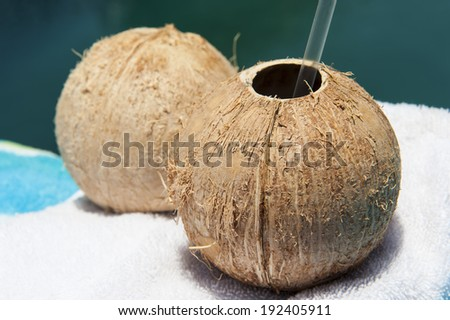 Two coconuts ready for drinking next to a pool in the sunshine - stock photo